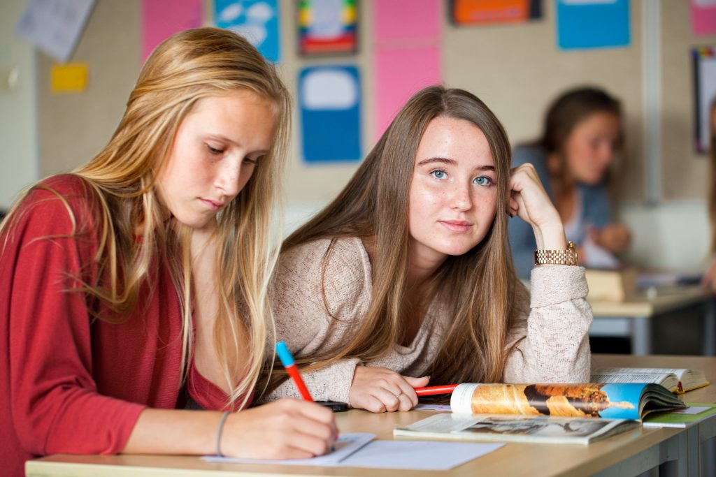 To tenåringsjenter som sitter på skolebenken